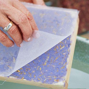 Step 6: Place the mold screen side up in a tub filled with 3 inches of water. Top the mold with the deckle and hold it down so the water rises to about 1 inch from the top. Pour the pulp into the deckle, using your free hand to evenly distribute the pulp over the screen.