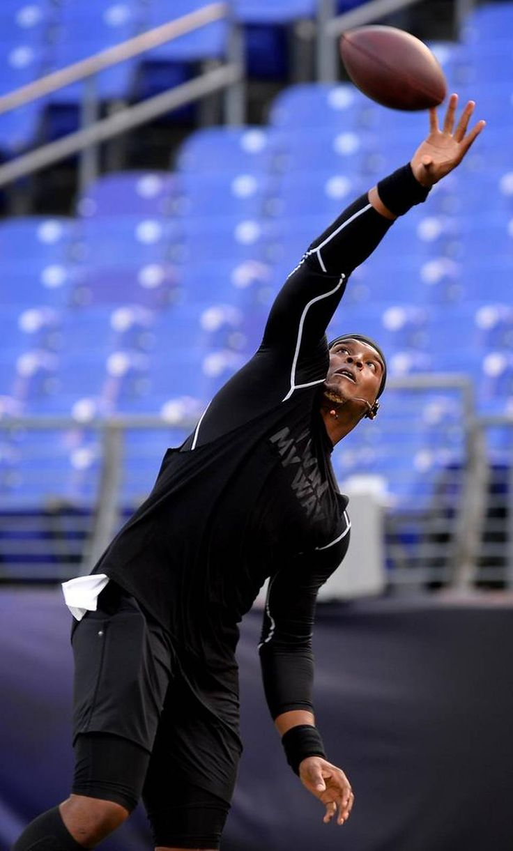 Carolina Panthers quarterback Cam Newton leaps to catch a football while warming…