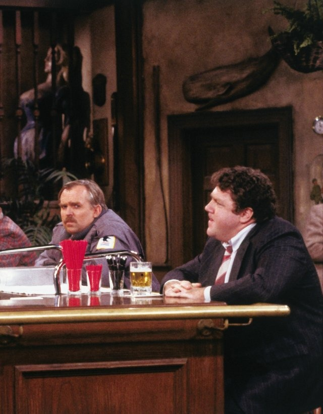 "Cliff Claven (John Ratzenberger) and Norm Peterson (George Wendt), in their seats at the ""Cheers"" bar."