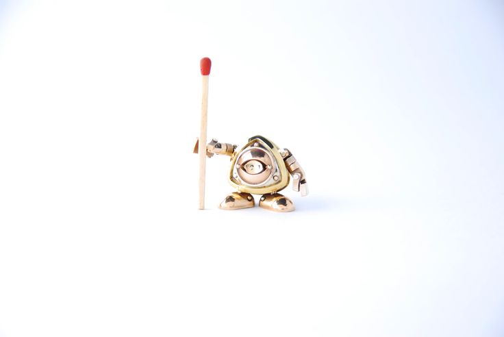Brinky by Juhani Ananin. Steampunk miniature made from brass, nickel brass, bronze, silver rivets and with a 18 karat gold plate set inside the eye. 2 x 2,5 x 1,5 cm  Umm... what do you plan to do with that match?  Photo: Hanna Silander