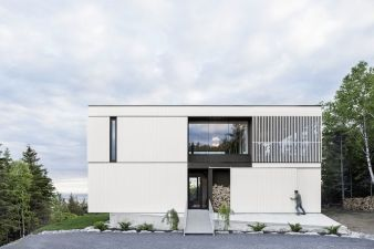 Perched on the podium, the upper two levels are clad in a white stained wood