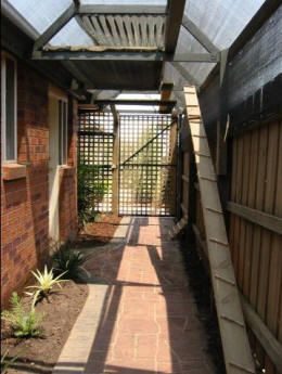 cat enclosure, side of the house, only need to bring up the 3 sides on the current fence and gates