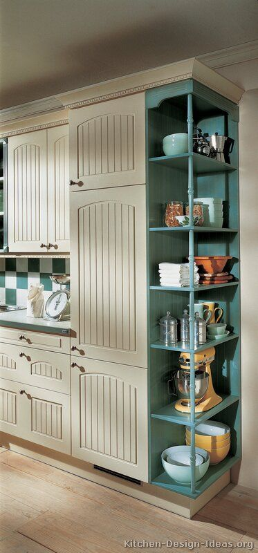 Beautiful custom-made kitchen cabinetry. Love the bead board, and the turquoise open shelving for appliances, etc., that frees up counter space. Very well-thought-out storage.