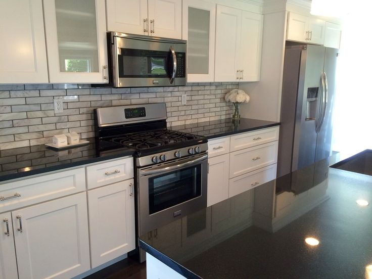 Transitional Black & White Kitchen by BlankSpace LLC, Pittsburgh PA. White Maple Cabinets by Wolf Classic Cabinetry, Absolute Black Granite and Marble 2x8 Subway Tile Backsplash. Glass Door Accents & Polished Nickel Hardware.