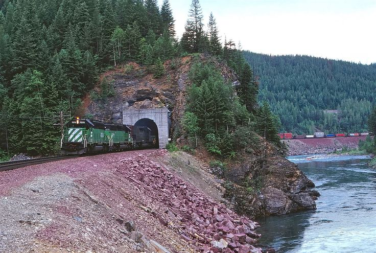 https://flic.kr/p/PYbAaX | BN 7076                  6-88 | An eastbound stack train exits a short tunnel along the middle fork of the Flathead river on the climb up Marias Pass.West Glacier MT
