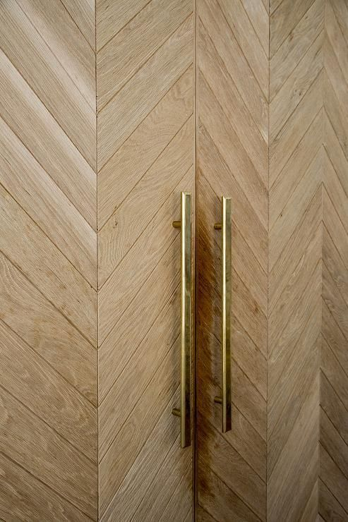 Dana Benson Construction - Wood herringbone paneled refrigerator doors are accented with long brass handles.