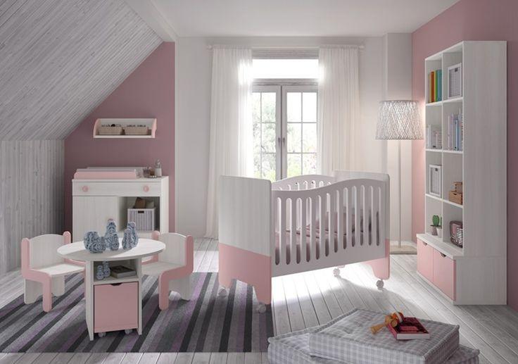 Une chambre très mignonne pour votre nouveau-né dans les tons rose clair avec un berceau, une petite table et deux chaises pour enfants, une bibliothèque avec coffre à jouets et une commode avec matelas à langer