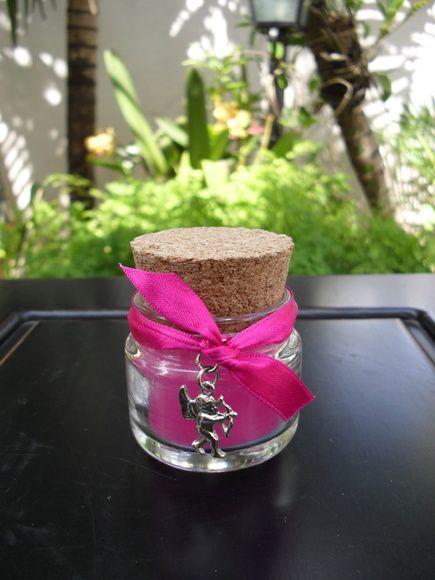 Vela em potinho de vidro com acabamento em fita de cetim (+ 1 pingente), mas cores azul, magenta ou pink. Duração aproximada 5 horas. Acompanha 1 saquinho em organza branca. R$ 5,10