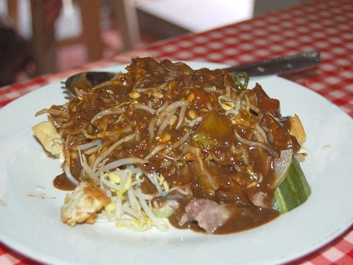 Rujak Cingur is a traditional food from East Java. Rujak Cingur a marinated cow snout or lips and noses (cingur), served with vegetable, shrimp prawn. It is then dressed in a sauce made of caramelized fermented shrimp paste (petis), peanuts, chili, and spices. It is usually served with lontong, a boiled rice cake.