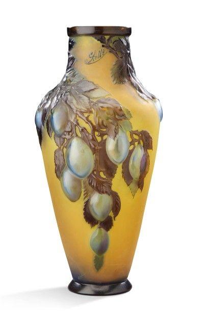 """EMILE GALLE (1846-1904) Vase de forme balustre en verre multicouche soufflé-moulé à décor en relief de quetsches bleues sur fond opaque jaune. Signé """"Gallé"""". Vers 1900. H: 39 cm (défaut de cuisson à la… - Aguttes - 29/09/2016"""