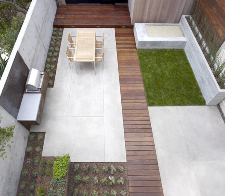 Strakke tuin/dakterras met betonnen en teakhouten elementen.