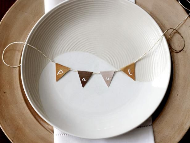 How to Make Customizable Thanksgiving Place Cards: These adorable little place card buntings will keep any table festive. Each mini bunting flag is for one letter. Type the letters onto the downloadable template, print on white card stock and then cut out the diamond shapes. Fold each diamond in two to make a triangle. Fold it across a piece of string or twine and at…: