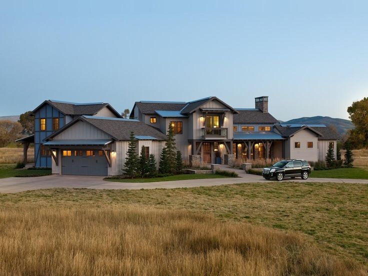 This sprawling rustic-modern ranch home in Utah features meadow-themed landscaping that connects to the home's mountain valley surroundings.
