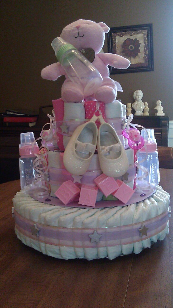 Diaper cake, made from diapers, onesie's, bibs, paci's, shoes, bottles, teddy bear and other toys.
