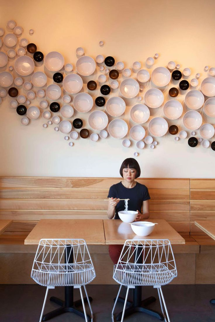 12 Ideas For Creating An Accent Wall Using Unexpected Materials | This Asian-American fusion restaurant has bowls installed on the wall to create a unique look that fits with what they serve.