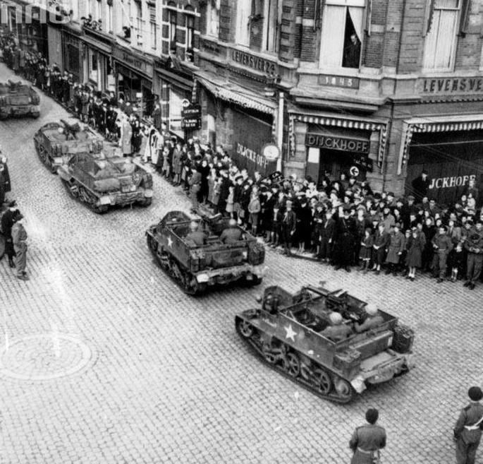 Carriers from the 3rd Rifles Brigade (1st Armoured Division) on one of the streets of Breda.