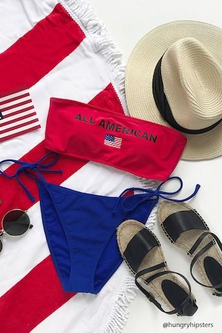 """A knit bandeau bikini top featuring a front """"All American"""" and USA flag graphic, a straight cut, an elasticized trim, removable cups, and a back hook closure. Matching bikini bottoms available."""