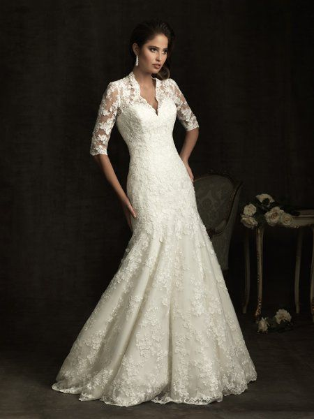 Wedding Dress - Lovely in lace. A slim A-line gown featuring lace applique throughout. The bodice features a v-shaped neckline 3/4 length sleeves with sheer lace details that continue to the fully covered back. Covered buttons and a sweep train complete this style.