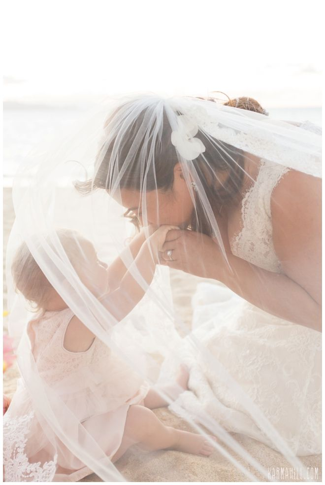 We cannot get enough of this adorable photo of a bride with her baby at a Hawaii Beach wedding -- absolutely beautiful! :: Wedding Photography :: Flower Girl Ideas :: Baby at a wedding :: Veil Photos :: Wedding Portraits :: Beach Wedding Photography