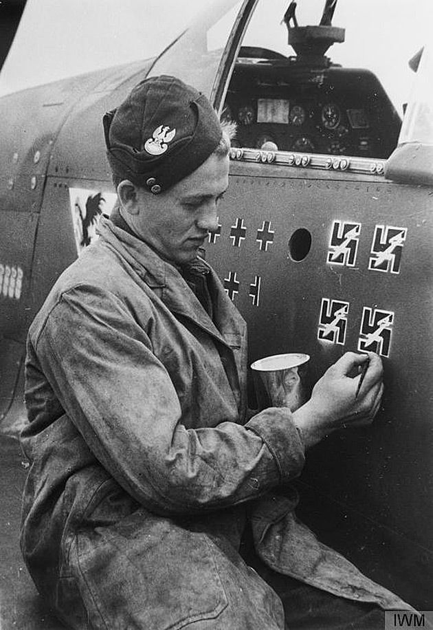 "Polish RAF Squadron Leader Eugeniusz ""Dziubek"" Horbaczewski transferring his confirmed ""kill"" icons to his newly-delivered P-51 Mustang at Brenzett (August 3, 1944). He was shot down and killed two weeks later on August 18, 1944. Note that the German crosses signify enemy airplanes, while the swastikas signify V1 rocket bombs."