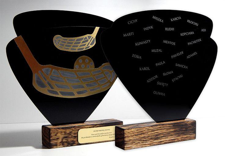 Statuetka sportowa na zawody w hokeju wykonana z połączenia trzech różnych materiałów: eleganckiej pleksi, drewna i nowoczesnego laminatu.