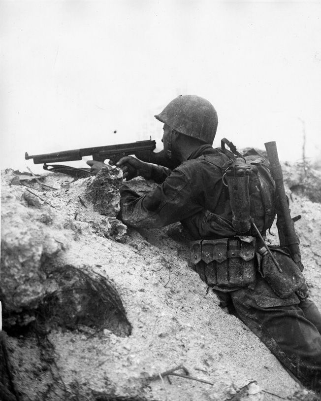 A Marine fires his Thompson submachine gun at Japanese positions from the shelter of a sandbank on Peleliu.