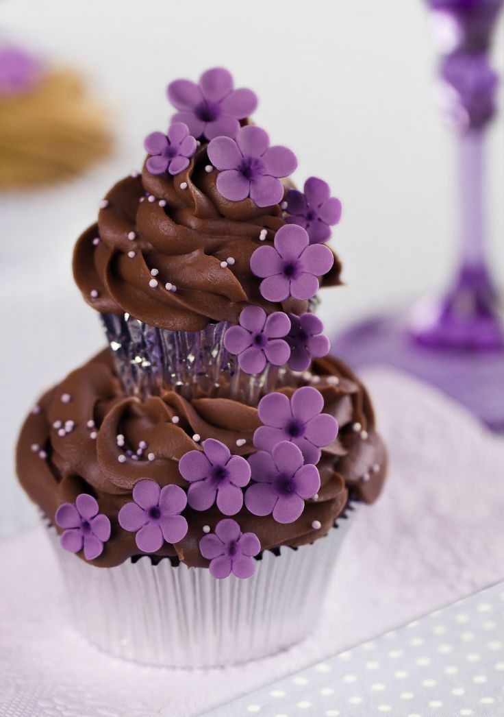Make these cupcakes by making a regular chocolate cupcake and stacking a miny cupcake on top. Making fondant out of marshmallows and food colouring you can mold tiny flowers onto toothpicks. Arrange as you see.