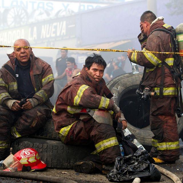 Pompieri si riposano dopo avere spento l'incendio. La Terminal è il più grande mercato di Città del Guatemala e le fiamme hanno distrutto molti negozi
