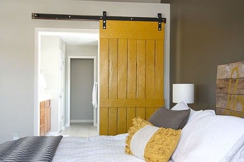 Yellow and grey, barn door and pallet or fence wood headboard. Master bedroom