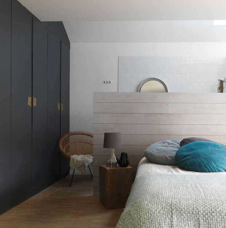 Une tête de lit en bois qui sert également de séparation entre le coin nuit et le coin salle d'eau d'une chambre parentale.