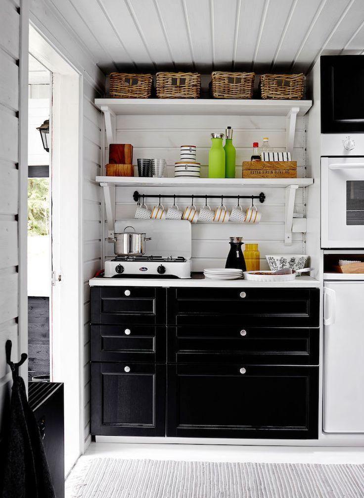 Tämän mökin pintaremontti tehtiin nopeasti ja kustannustehokkaasti uusimalla kaapistot. Keittiön hyöty on maksimoitu muun muassa avohyllyillä. Varsinainen ruoanlaittopaikka sijaitsee ulkona.