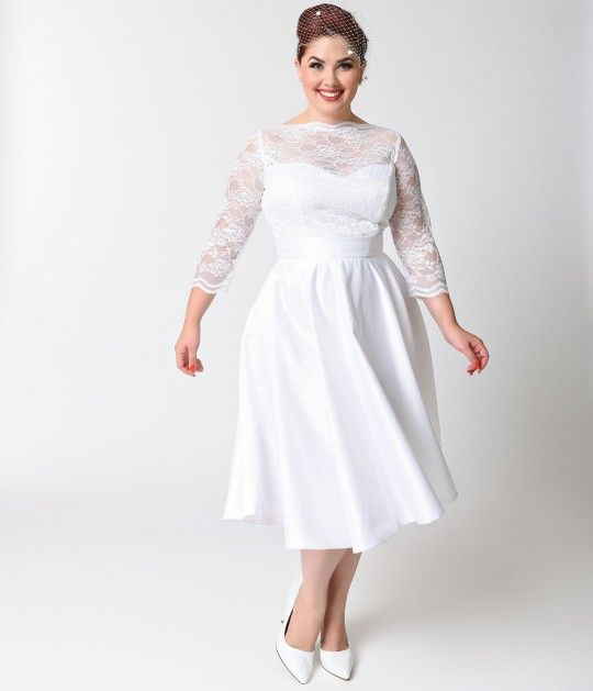 A vintage vision fresh from Heart of Haute and Bettie Page Bridal, the white lace and satin 1950s Colette wedding dress is a plus size retro design that is truly heart stopping. A scalloped sheer high lace neck is fitted and met with sheer three-quarter s