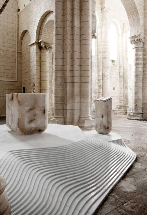 French designer Mathieu Lehanneur has added stacked layers of white marble to create a podium in this Romanesque church in France.St Hilaire church in Melle