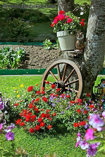 Jazz encima de la cama de flores que rodea un árbol w / Accesorios rústicos (rueda de carro, carretilla, silla de madera), colgar plantas en macetas en el tronco y colocar estratégicamente lámparas de jardín de energía solar en estacas a lo largo del perímetro de la cama de flor .: