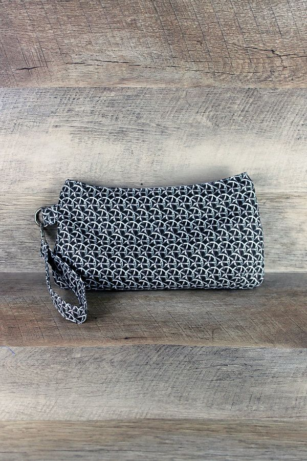 A bag to hold the bare essentials for a night out on the town!  Makes a wonderful gift!  Black and grays nautical stars/western stars Coraline clutch/wristlet with a recessed zipper and gray and white swirl interior. Includes detachable wristlet strap.  Measures approximately 10.5 at widest point b
