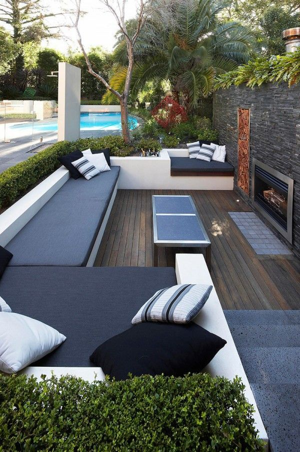 bench seating incorporating landscaping, pool and fireplace #outdoorliving