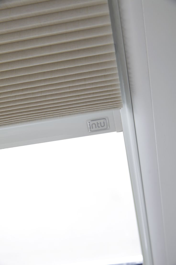 Taupe pleated Intu blinds from Apollo Blinds - a unique tension system prevents the blind from rattling against the glass.