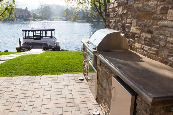 Fully equipped #barbecue with counter and fridge. The floor is made of concrete brick pavers and in the background concrete slabs make a path to the dock. #patio #bbq #patiodesign #patiodecor #patioideas