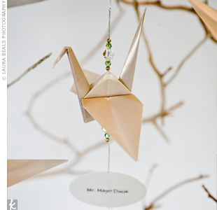 some of the 1001 to be used as name cards, hang them from the branches on the center piece at the table?
