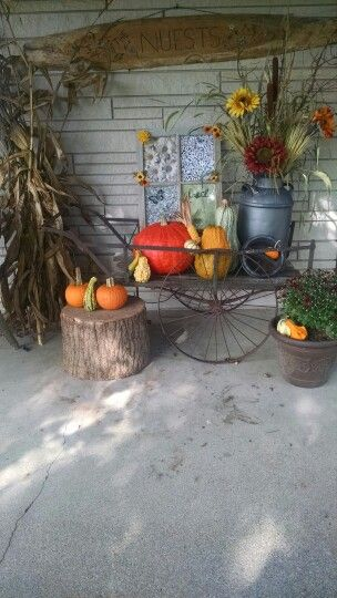 An old wagon, milk can, window and a hunk of wood completes the Fall theme on this porch.