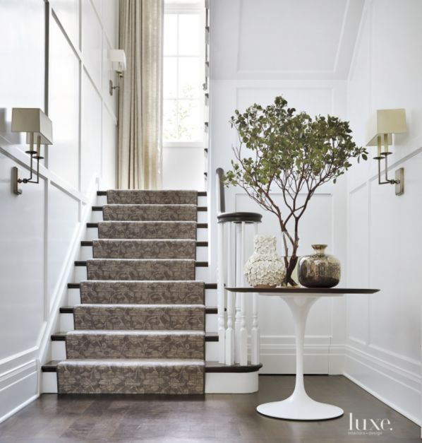 Elaborate millwork and a handsome wool runner with a floral pattern from Watson Smith define the aesthetic in the stair hall at the back of the house. A Saarinen table from Knoll sits front and center and is joined by Visual Comfort's sleek double-arm sconces for a bit of modern edge in the otherwise traditional space.