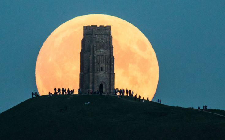 Суперлуна восходит за холмом Святого Михаила в графстве Сомерсет, Англия.