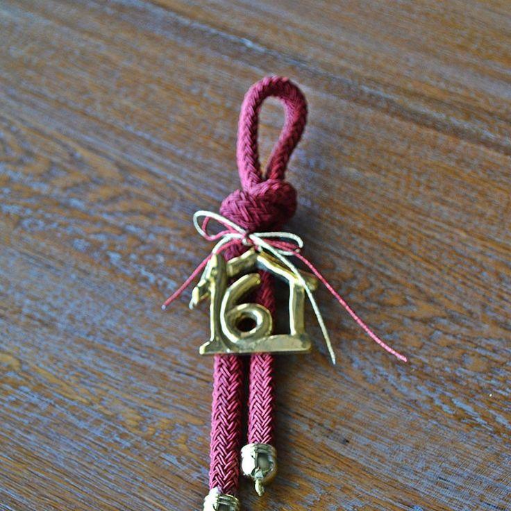 Γούρι μπρούτζινο σπίτι 16 με μπορντώ κορδόνι με μοναδικό κόμπο και μεταλλικά στοιχεία.