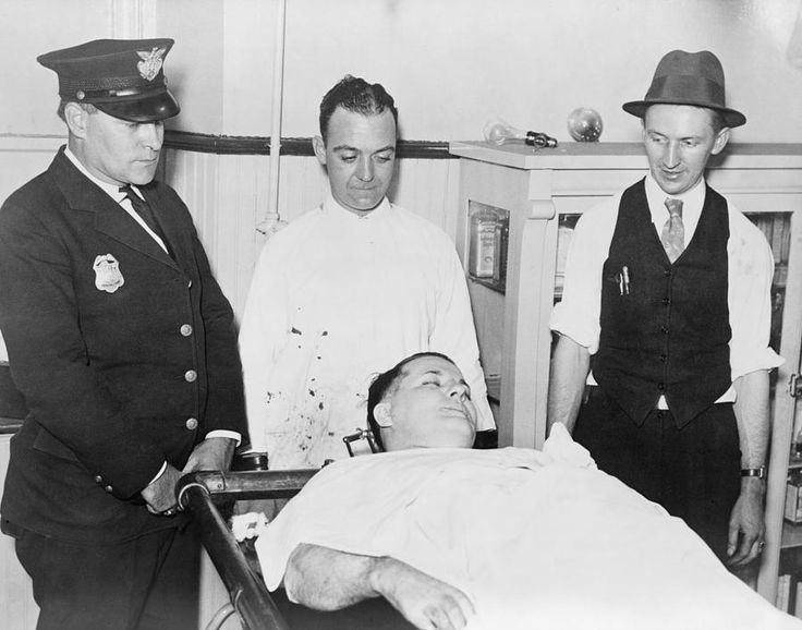 Dead body of Charles 'Pretty Boy' Floyd (1904-1934) on a gurney with police officers Robert Pyle and George Curran, and undertaker Frank Dawson standing nearby. He was shot dead by Melvin Purvis and other FBI agents. Channing Tatum played 'Pretty Boy' Floyd in the 2009 film, 'Public Enemies'.