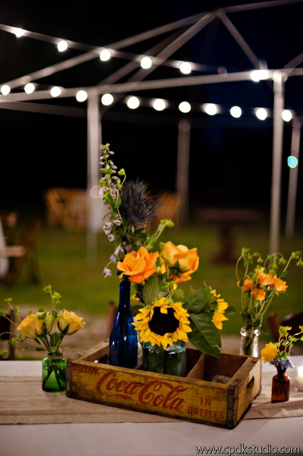 Vintage coke crates, wildflowers and antique bottles for centerpieces   -Young Wedding  pic by http://www.cpdkstudio.com/  Captured Photography Oxford MS