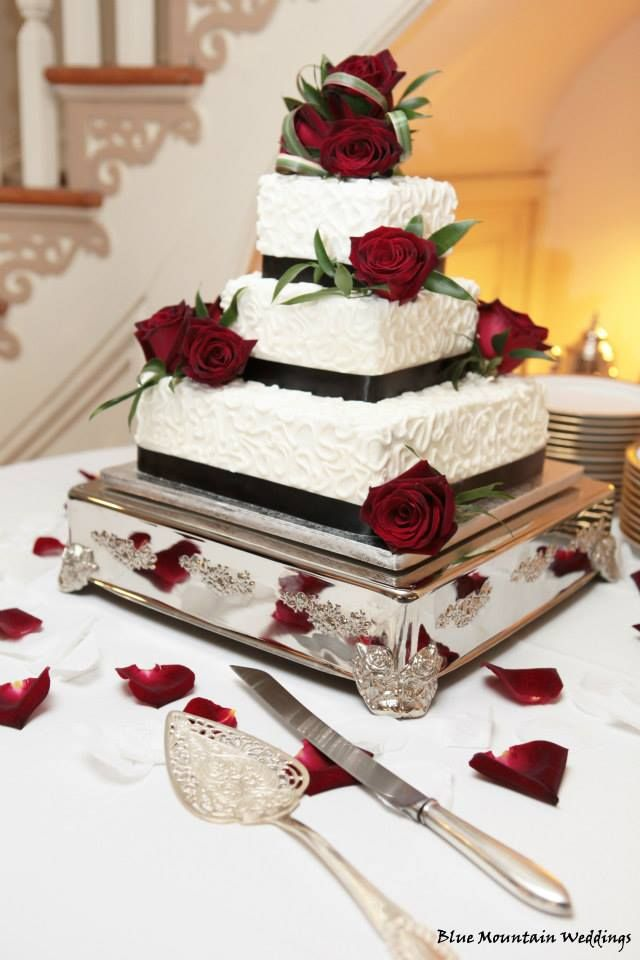 Red velvet wedding cake with buttercream icing and crimson red roses.