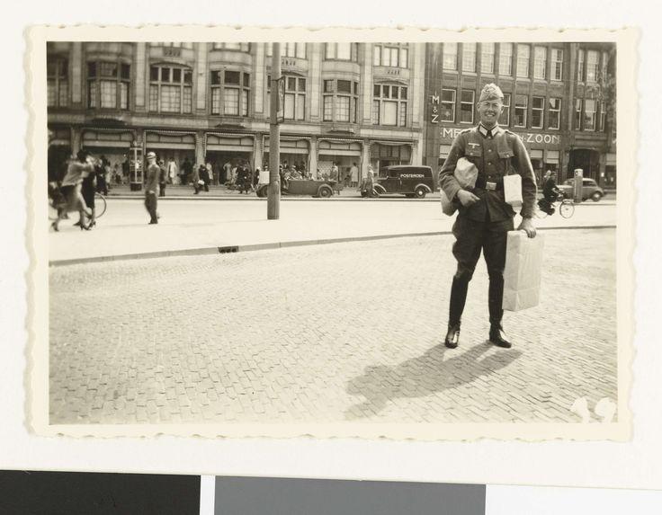 Anonymous | Duitse soldaat met kadootjes, Anonymous, 1940 - 1943 | Een Duitse soldaat, met legerpet en bril, staat midden op de Hofweg (tegenover het Binnenhof) in Den Haag met drie pakjes. Achter hem huizen en winkels, o.a. Meddens en Zoon en voetgangers. Het lijkt weer dezelfde persoon als op de nrs. NG-2007-5-35 t/m38
