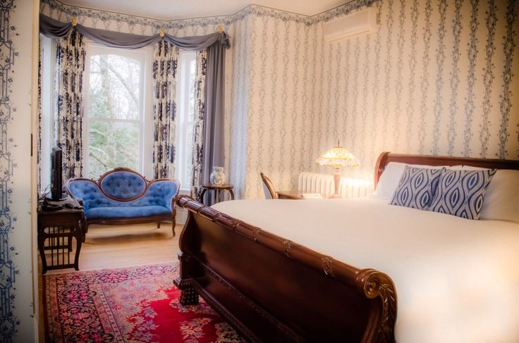 Room with a king size bed and large bay windows at Queen Anne Inn.