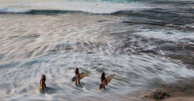 O surfe liga os havaianos à sua identidade cultural. Assim que o dia amanheceu, duas irmãs e um primo foram surfar em Makaha, na Ilha Oahu, Havaí, USA, para se aquecer para uma competição.  Fotografia: Paul Nicklen /National Geographic. Creative.
