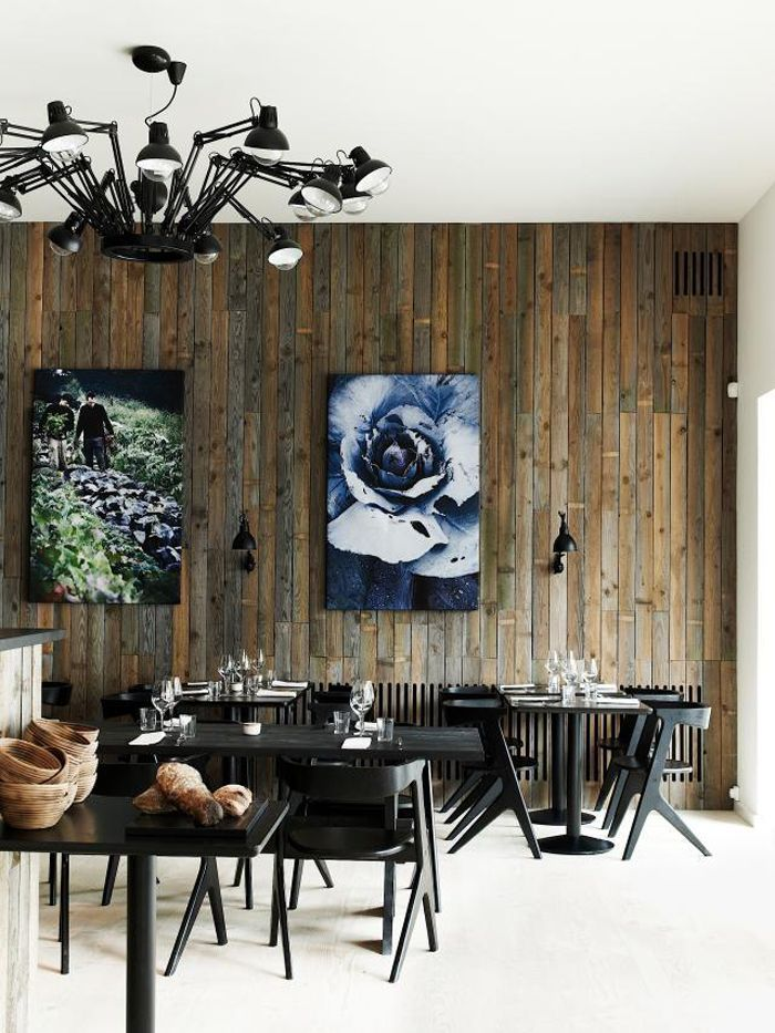 Recycled timber walls with sleek black furniture and big food related prints at Radio Copenhagen.
